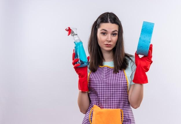 Mooi meisje in schort en rubberen handschoenen met schoonmaak spray en spons camera kijken met sceptische uitdrukking