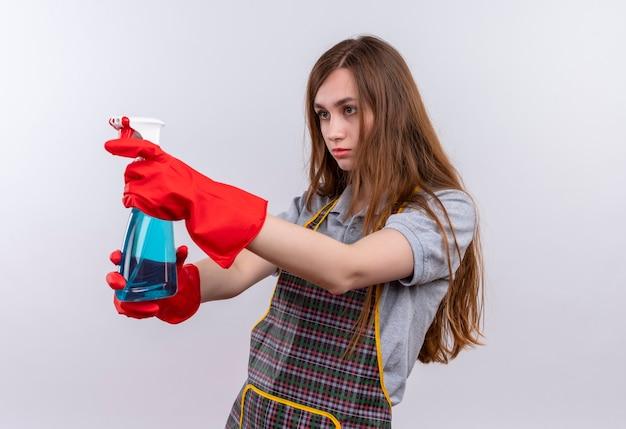 Mooi meisje in schort en rubberen handschoenen met schoonmaak spray gericht met het
