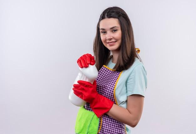 Mooi meisje in schort en rubberen handschoenen met schoonmaakproducten en tapijt camera kijken met zelfverzekerde glimlach