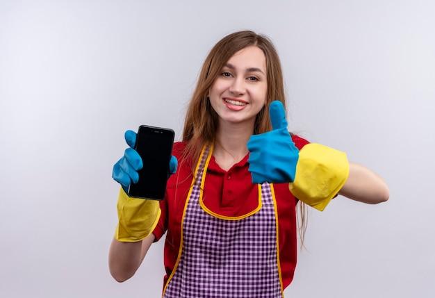 Mooi meisje in schort en rubberen handschoenen met smartphone duimen opdagen glimlachen
