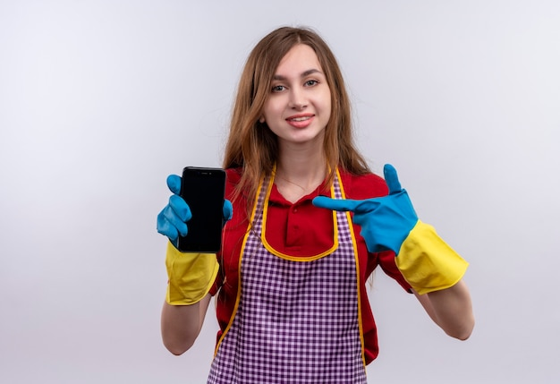 Mooi meisje in schort en rubberen handschoenen met smartphone wijzend met vinger naar het glimlachen