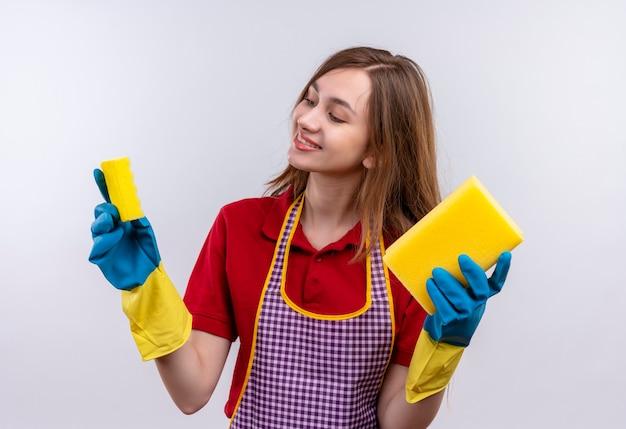 Mooi meisje in schort en rubberen handschoenen met sponzen kijken naar hen glimlachend