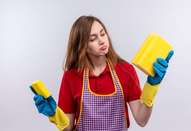 Mooi meisje in schort en rubberen handschoenen met sponzen kijken naar hen onzeker en verward proberen een keuze te maken