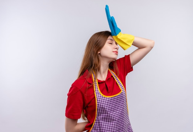 Mooi meisje in schort en rubberen handschoenen op zoek moe en overwerkt met hand op hoofd