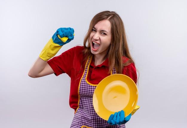 Mooi meisje in schort en rubberen handschoenen plaat met behulp van spons wassen, schreeuwen met agressieve expressie