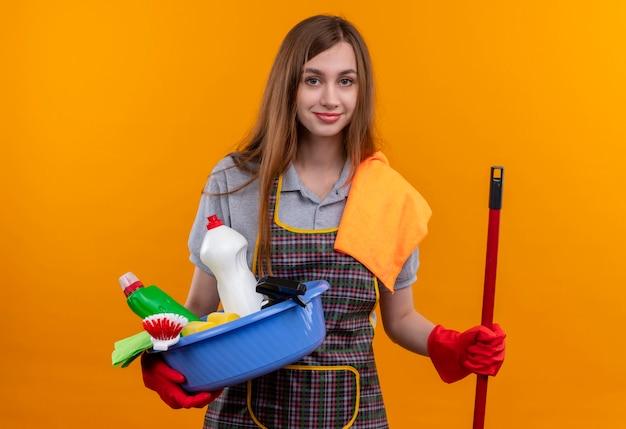 Mooi meisje in schort en rubberhandschoenen die bekken met het schoonmaken van hulpmiddelen houden en zelfverzekerd glimlachen dweilen