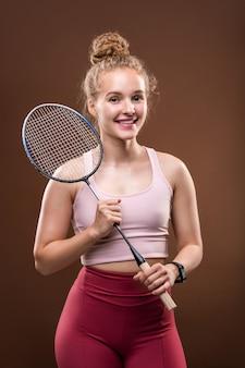 Mooi meisje in sportkleding tennisracket houden en op zoek naar jou met brede glimlach