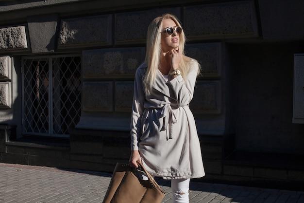 Mooi meisje in stijlvolle zonnebril en met een modieuze tas bij zonsondergang.