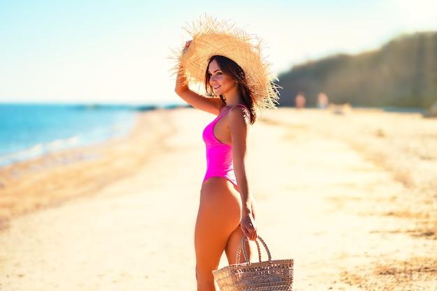Mooi meisje in strohoed en roze bikini loopt op een zonnige dag over zeewit zand terwijl ze een strandtas vasthoudt