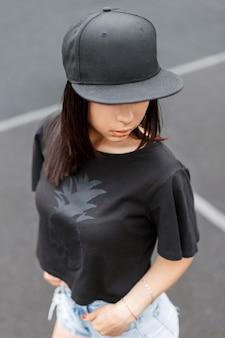 Mooi meisje in swag-stijl zwart t-shirt en een pet in het stadion.