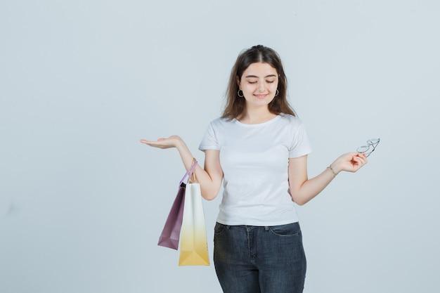 Mooi meisje in t-shirt, spijkerbroek cadeauzakjes te houden en op zoek vrolijk, vooraanzicht.