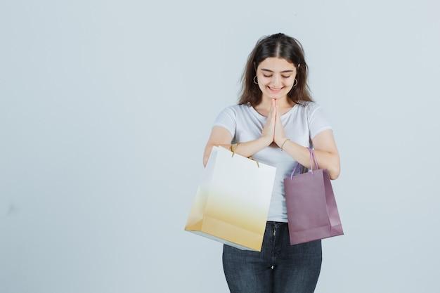 Mooi meisje in t-shirt, spijkerbroek met namaste-gebaar, houdt papieren zakken vast en kijkt dankbaar, vooraanzicht.