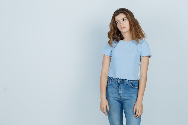 Mooi meisje in t-shirt, spijkerbroek wegkijken en op zoek moe, vooraanzicht.