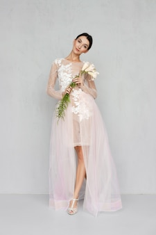 Mooi meisje in transparante tule jurk met kant poseren met bloemen in de hand