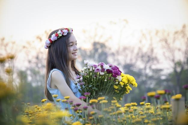 Mooi meisje in uitstekende kleding en hoed die zich dichtbij kleurrijke bloemen bevinden
