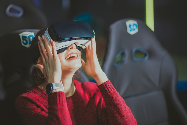 Mooi meisje in virtuele bril kijkt naar een film met speciale effecten
