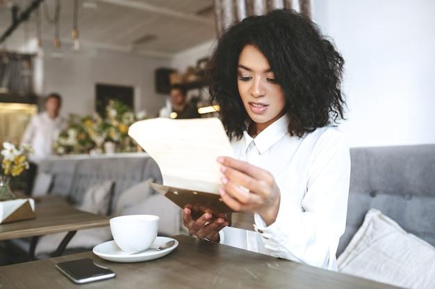 Mooi meisje in wit overhemd zittend in restaurant met menu in handen