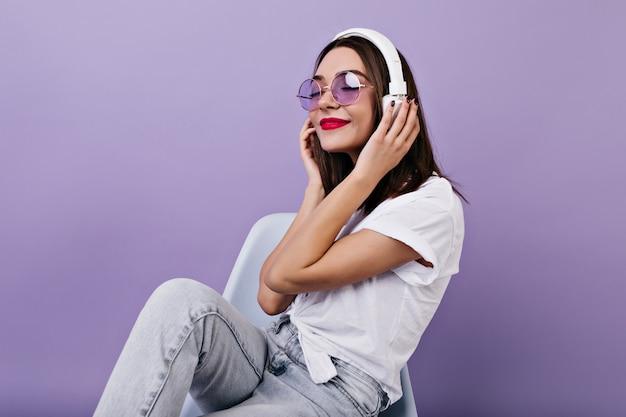 Mooi meisje in wit t-shirt luisteren muziek. binnen schot van schattige brunette vrouw genieten van lied met gesloten ogen.