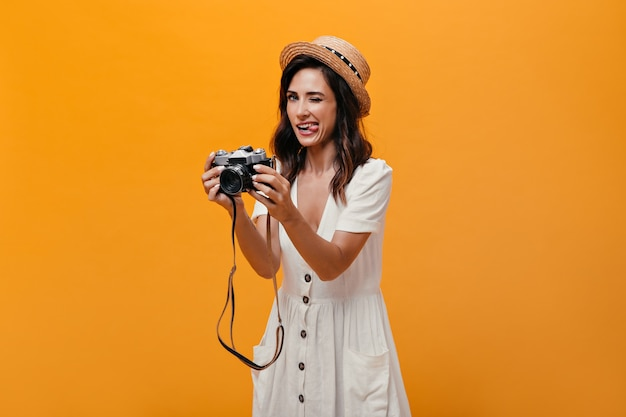 Mooi meisje in witte jurk en hoed toont tong en houdt retro camera. grappige vrouw in zomer lichte outfit met kort haar poseren.