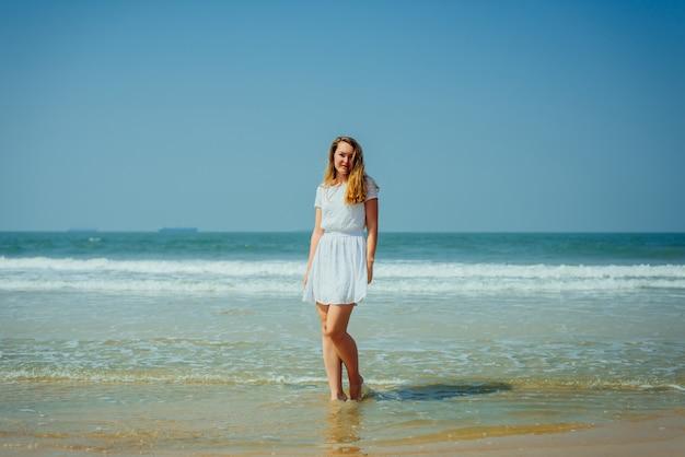 Mooi meisje in witte jurk geniet en ontspannen op het strand tijdens vakantie
