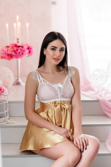 Mooi meisje in witte kanten boudoirjurk op de achtergrondkleuren decor met groot raam