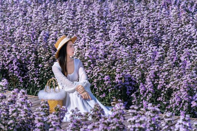 Mooi meisje in witte kledingszitting in de bloemenvelden van margaret