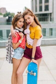 Mooi meisje in witte oortelefoons en polshorloge huggs met schattige donkerharige zus met blauw skateboard