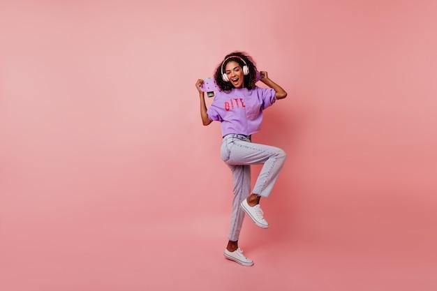 Mooi meisje in witte schoenen dansen in de studio terwijl u muziek luistert. portret van gemiddelde lengte van verfijnde afrikaanse dame met skateboard het koelen op roze.