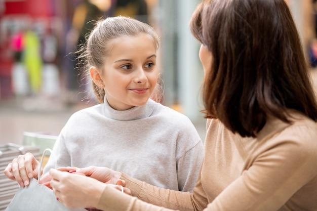 Mooi meisje in witte trui moeder kijken terwijl ze bespreken wat ze kochten op zwarte vrijdag uitverkoop in het winkelcentrum