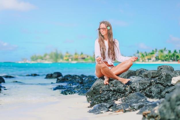Mooi meisje in yoga-positie tijdens tropische vakantie