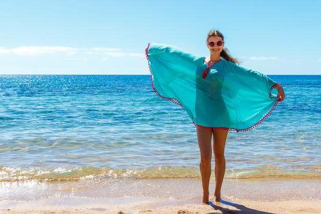 Mooi meisje in zee-stijl met plezier op een strand. reis- en vakantieconcept