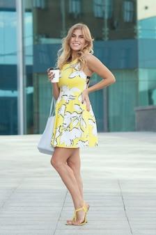 Mooi meisje in zomerjurk op straat met koffie in de ochtend
