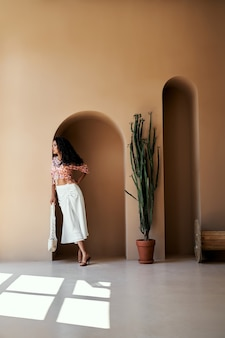 Mooi meisje in zomerkleding die bij de muur staat