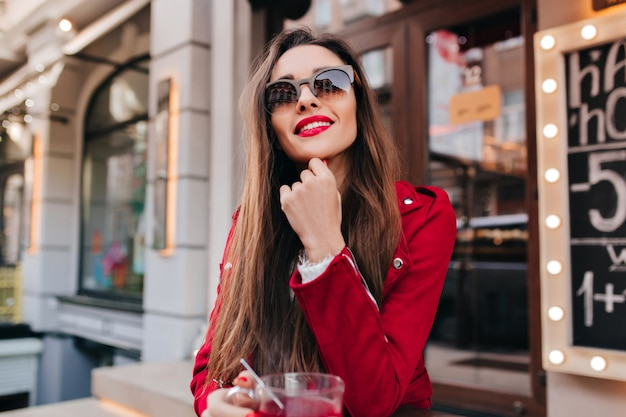 Mooi meisje in zonnebril en rode jas poseren met geïnteresseerde glimlach