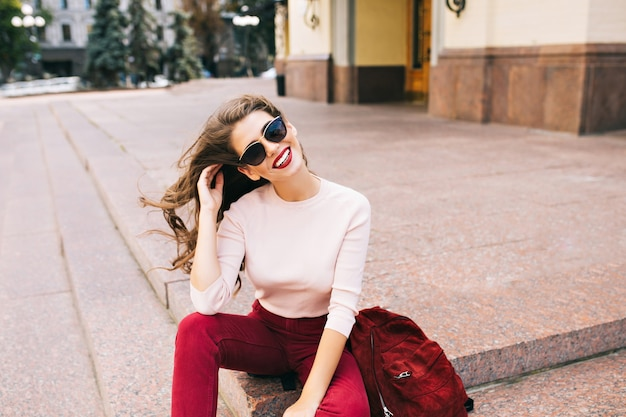 Mooi meisje in zonnebril in vineuse broek zit op trappen in de stad. haar lange haren vliegen door de wind, ze glimlacht.