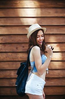 Mooi meisje in zonnebril poseren op bruine muur