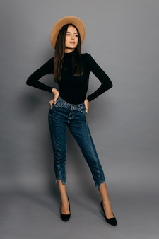 Mooi meisje in zwart pak, jean en strooien hoed, geïsoleerd op een grijze achtergrond. hoge kwaliteit foto
