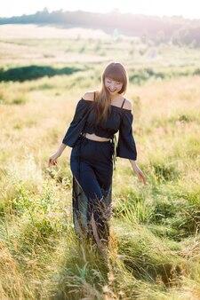 Mooi meisje in zwart pak wandelen en lachend buiten in een weiland tijdens zomer zonsondergang