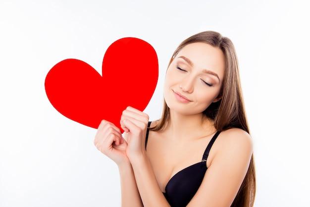 Mooi meisje in zwarte beha met papieren hart met gesloten ogen