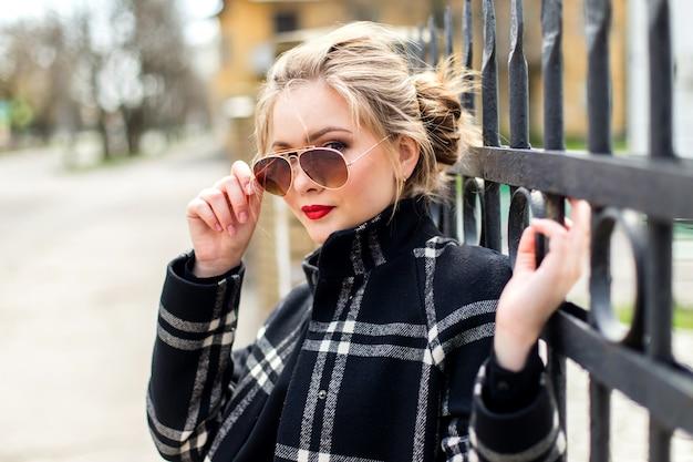 Mooi meisje in zwarte jas en zonnebril staan in de buurt van een smeedijzeren hek