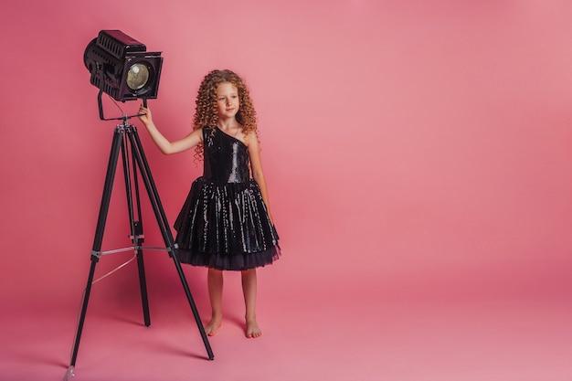 Mooi meisje in zwarte jurk op roze achtergrond in studio glimlachend en poseren