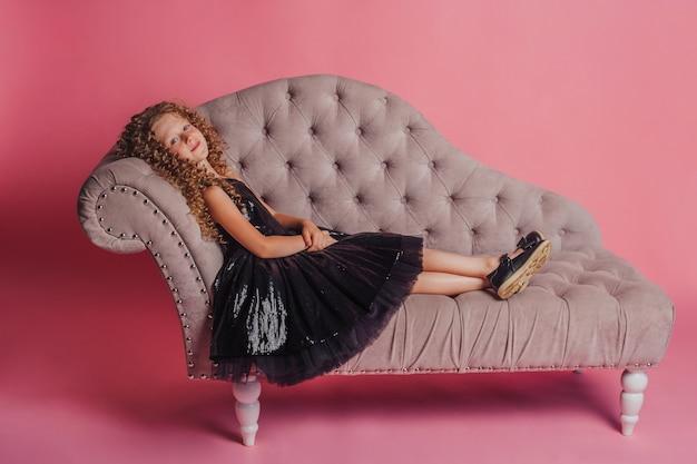 Mooi meisje in zwarte jurk op roze achtergrond in studio liggend op de bank