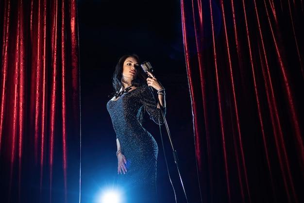 Mooi meisje in zwarte jurk zingen in de microfoon in de concertzaal
