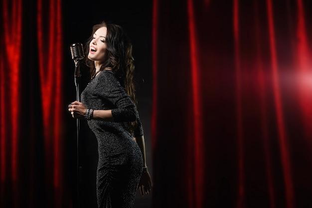 Mooi meisje in zwarte jurk zingen in de microfoon in het concertgebouw
