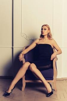 Mooi meisje in zwarte kleding en schoenen in antieke stoel retro drie kwart