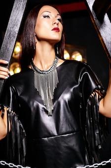 Mooi meisje in zwarte kleding poseren met studiolichten