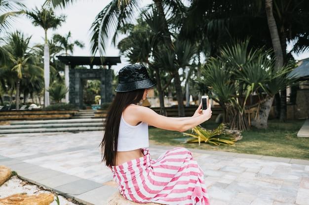 Mooi meisje in zwarte panama maakt selfie op een smartphone aan zee in een recreatiepark. vakantie in de tropen.