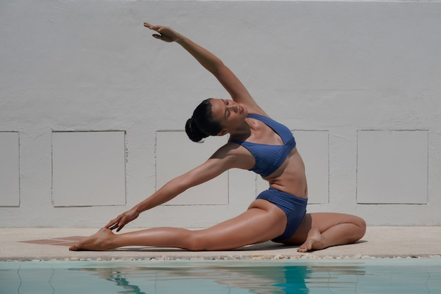Mooi meisje in zwembroek doet yoga bij zwembad, witte muur achtergrond, fitness concept.