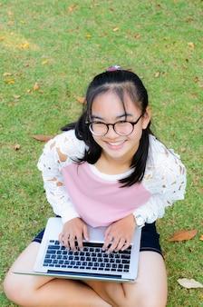 Mooi meisje is blij met een laptop op het gazon in het park