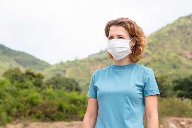 Mooi meisje, jonge vrouw in een medisch steriel beschermend masker op haar gezicht die frisse lucht ademen, die in bergen lopen. milieu-ecologie vervuiling probleem concept. kopieer ruimte. red onze planeet.